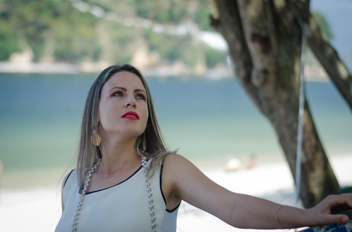bela Angelica olhando para o céu com o lindo mar atrás dela posando ao lado da árvore registrada pelo Estúdio Golau Fotografia de ensaio fotográfico Niterói RJ numa bela tarde