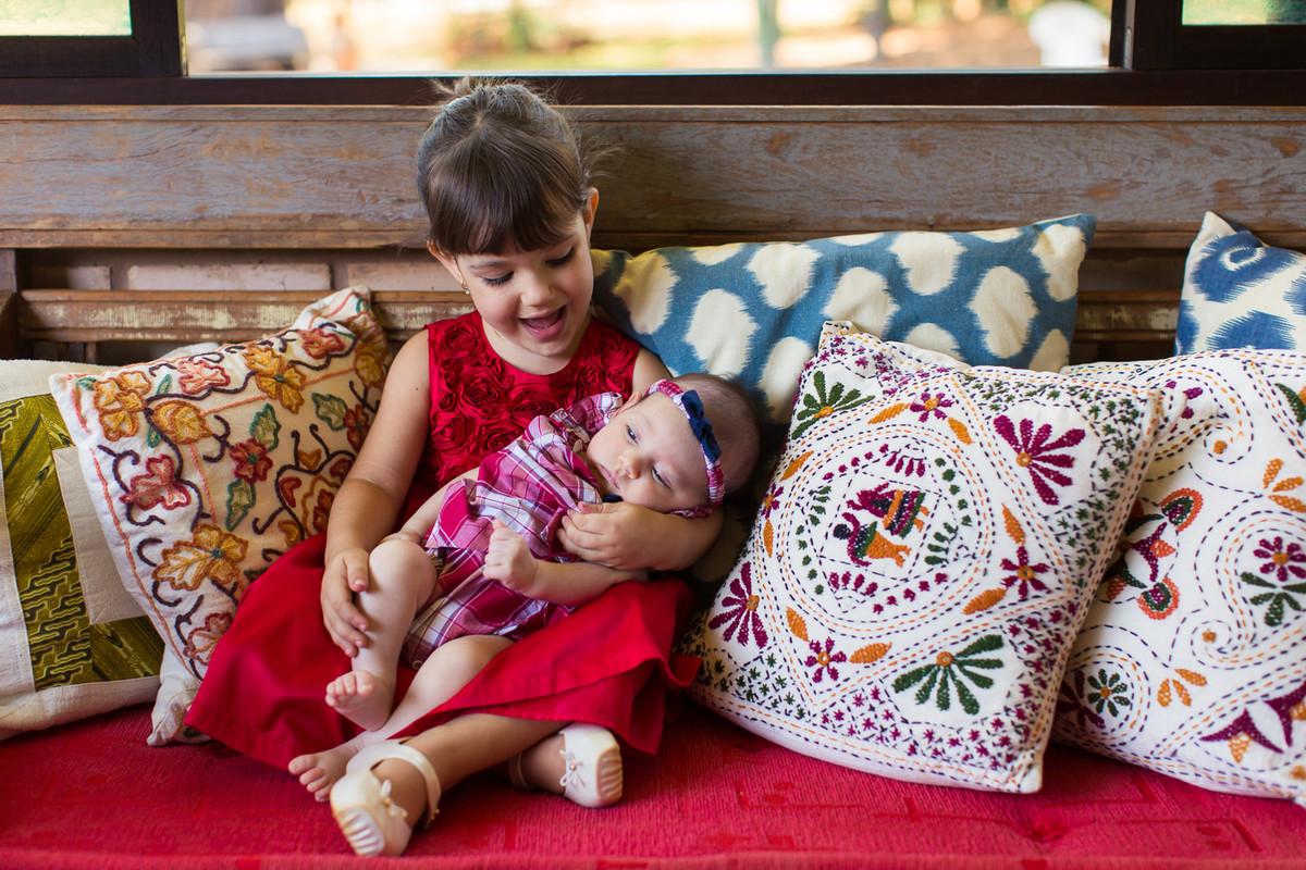 criança brinca no jardim de casa durante sessão fotográfica com sua irmã. fotografias feitas no lago norte, em Brasília