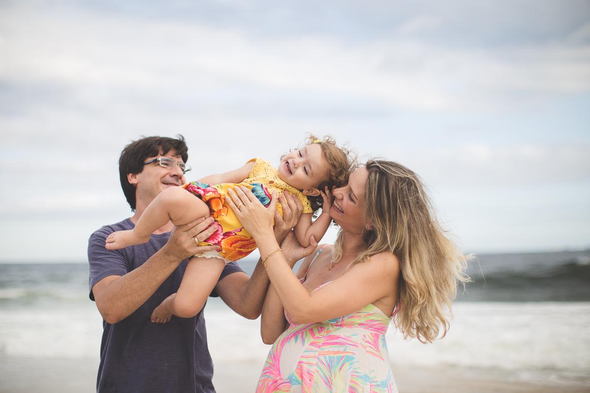 familia posa em praia no rio de janeiro para comemorar a gravidez e o novo filho. gravida mãe pai familia criança sessao de fotos