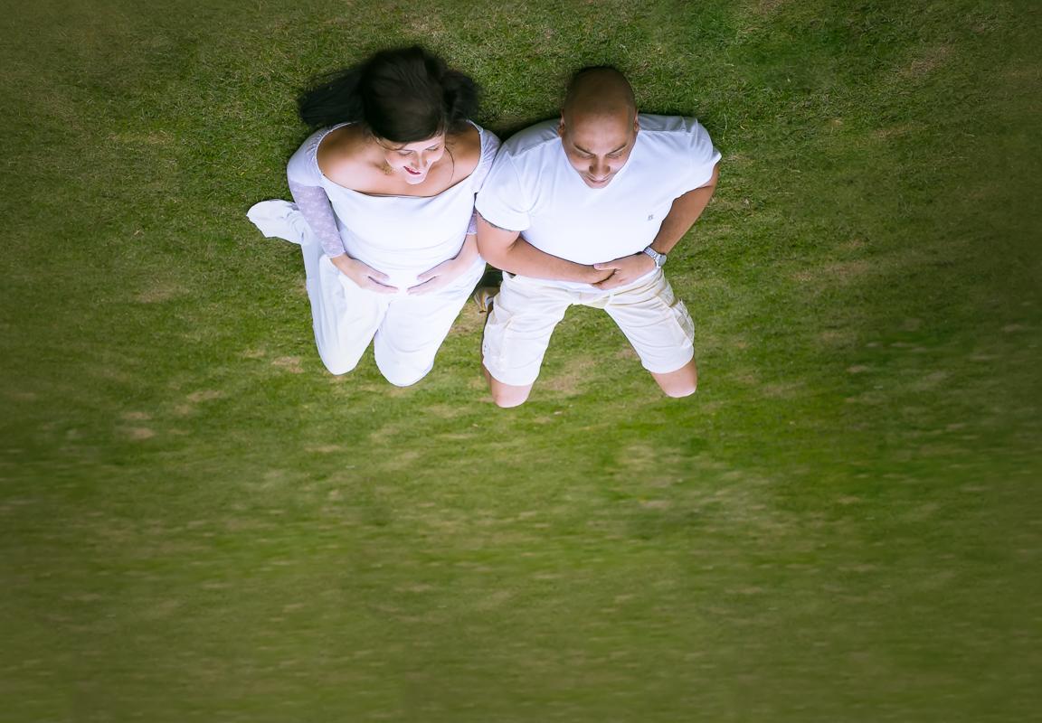 Fotografando gestante deitada no chão junto com esposo