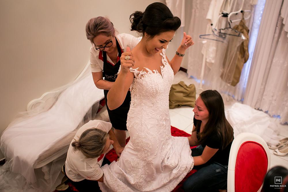 noiva colocando vestido