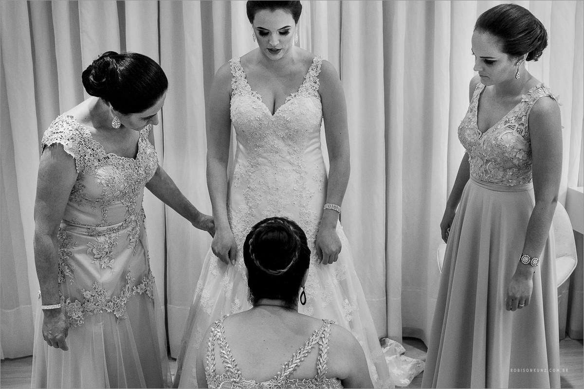 irmãs e mãe vestindo a noiva antes do casamento