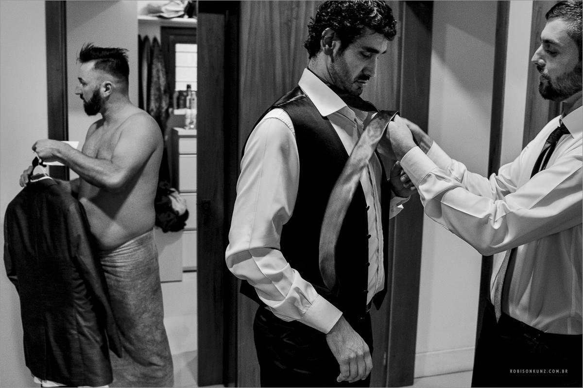 noivo e padrinhos se vestindo para o casamento