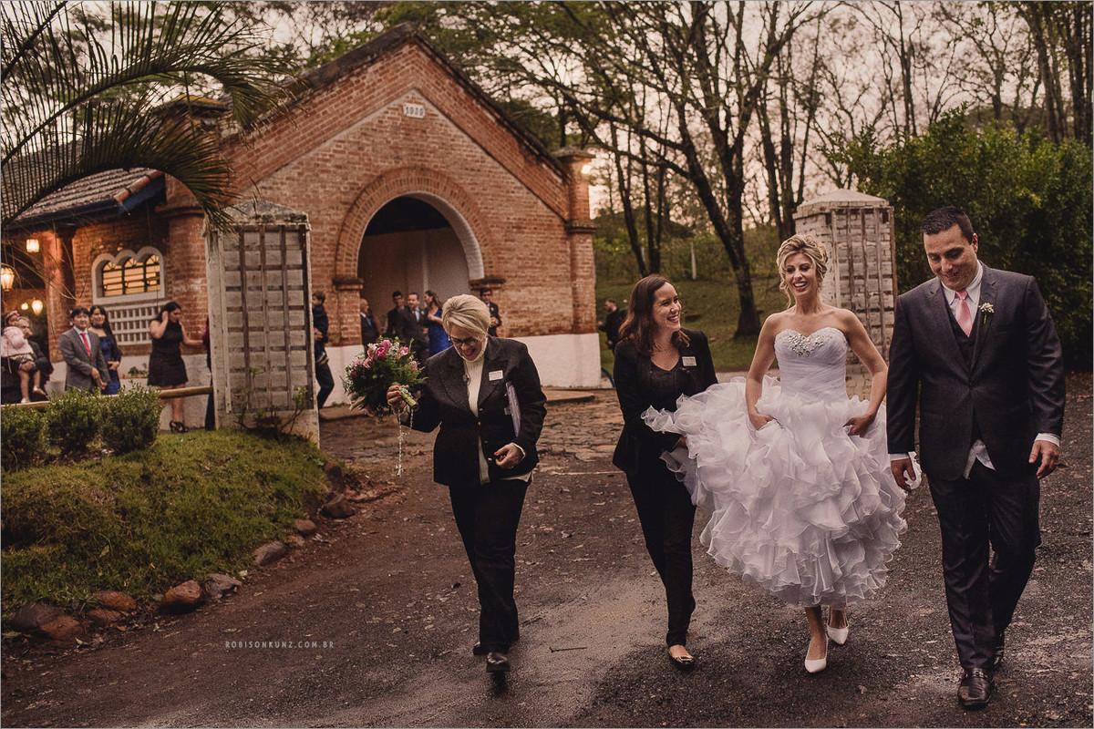 noivos saindo da cerimonia na chuva