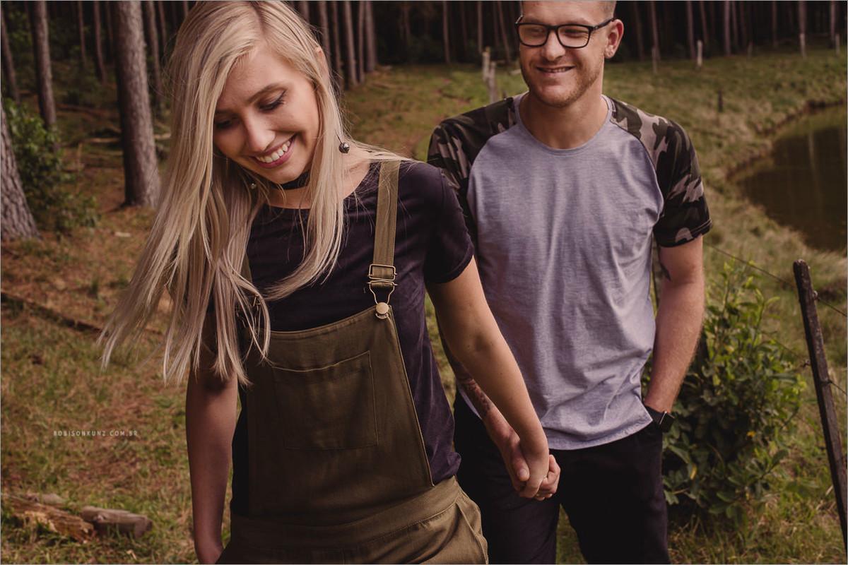 casal caminhando mato de pinos