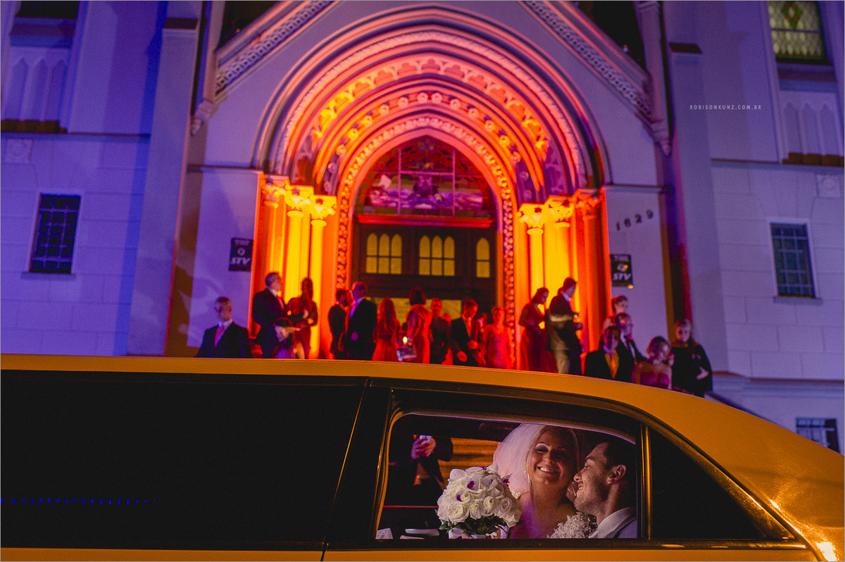 noivos com limousine na frente da igreja