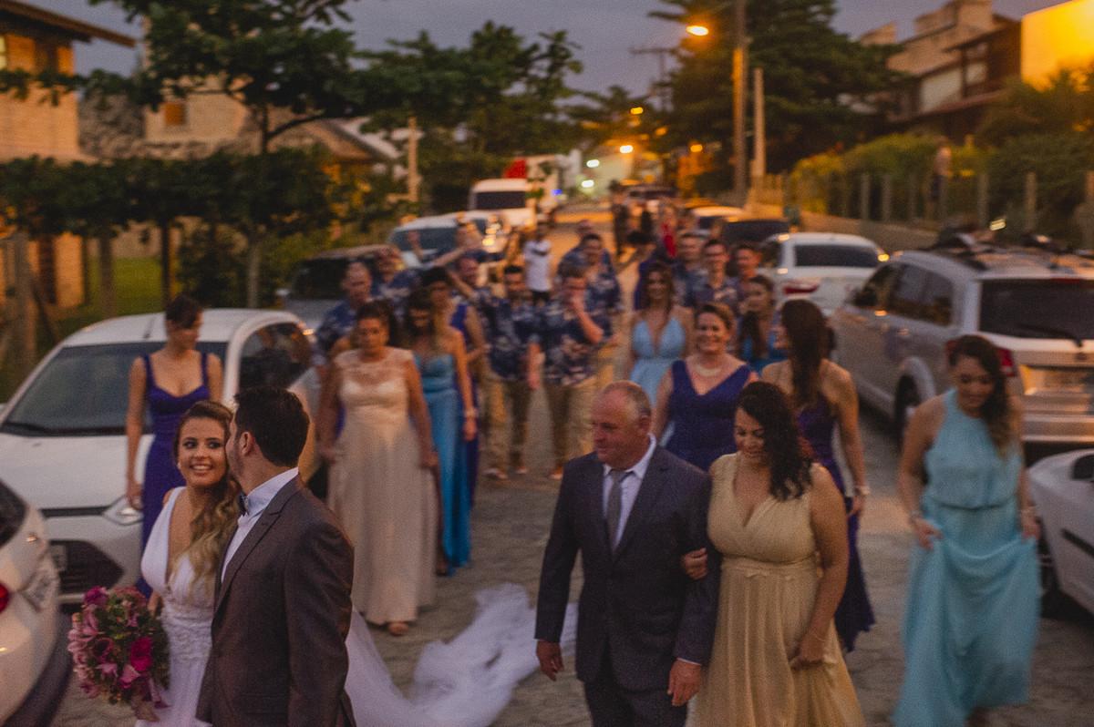 noivos e padrinhos andando na praia após o casamento
