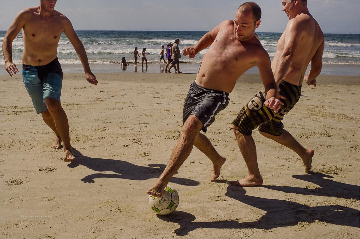 noivo e padrinhos jogando futebol na praia antes de começar o casamento