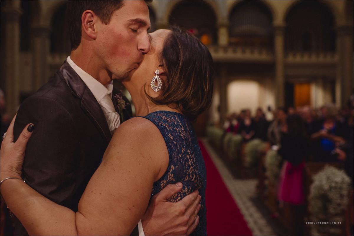 beijo do noiva e sua mae na entrada do casamento