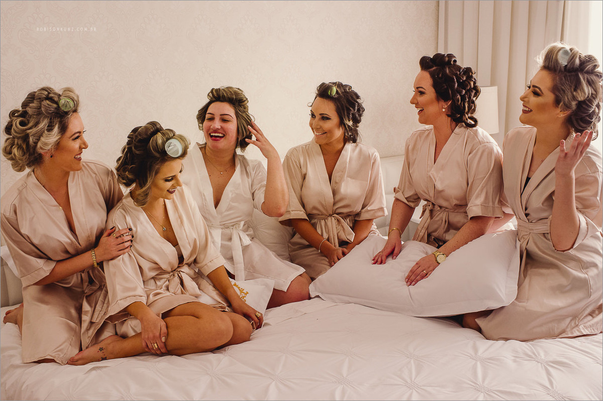 noivas e madrinhas na cama de hotel