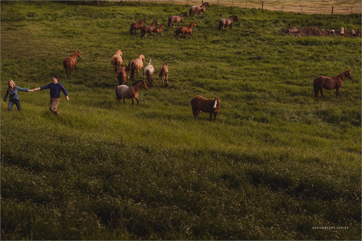 casal no meio do campo com cavalos
