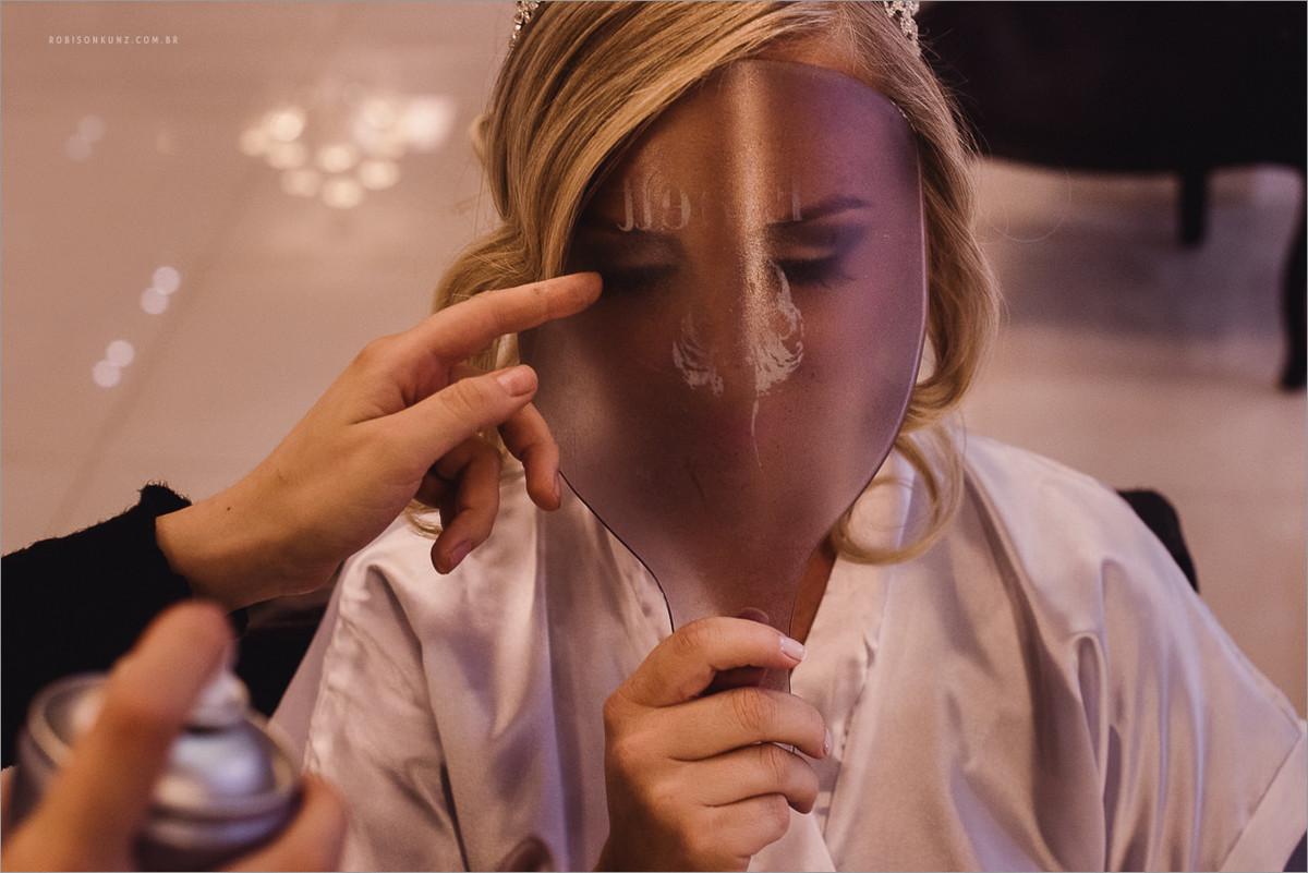 noiva sendo maquiada com mascara