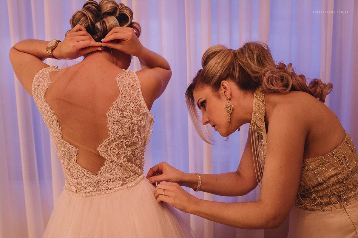 irmã ajudando a vestir a noiva