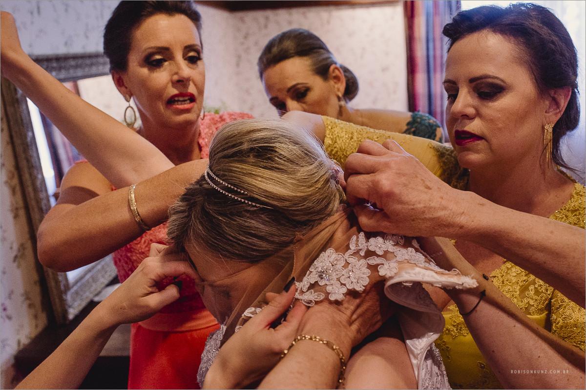 madrinhas ajudando a vestir a noiva