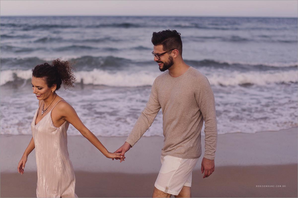 caminhando de mãos dadas na beira do mar
