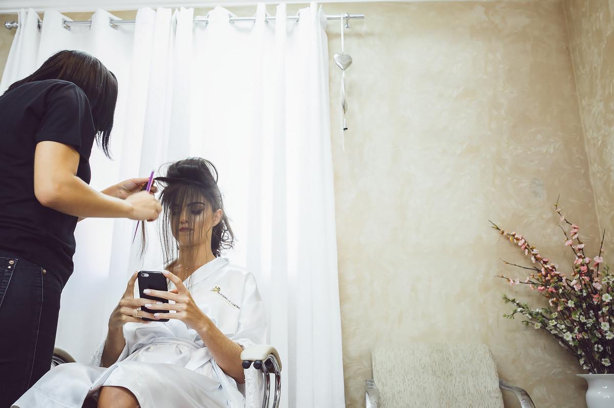 noiva sendo penteada e ao telefone Fotos de casamento Governador Valadares Josie Nader