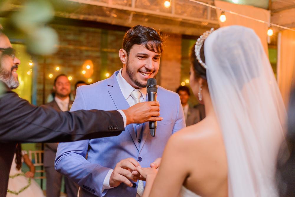 noivo sorrindo ao colocar a lindaça na noiva