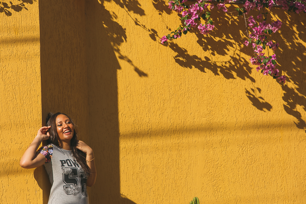 a menina no muro amarelo com flores, menina feliz, ensaio fotográfico