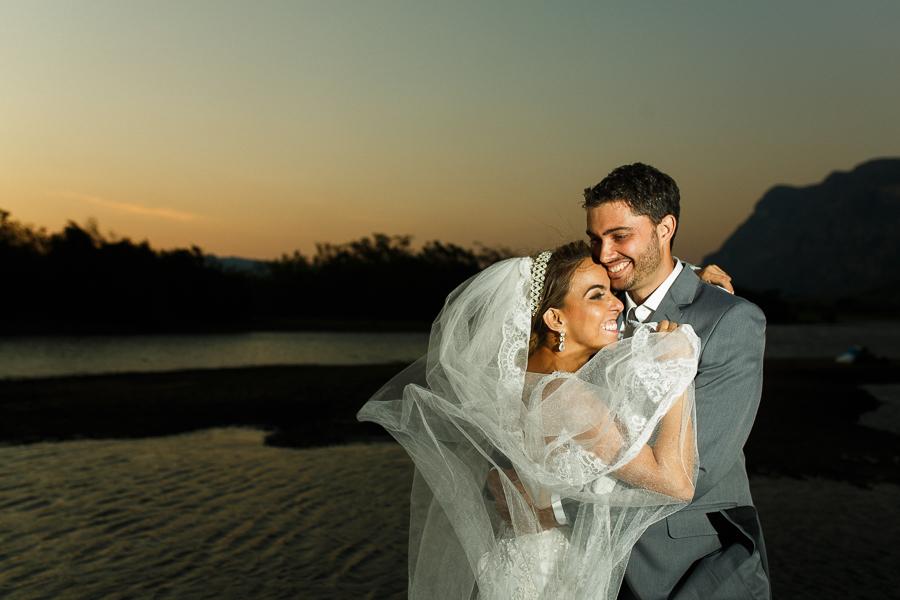 casal josiane e warley abraçados e sorrindo com o lago ao fundo,  lapinha da serra MG