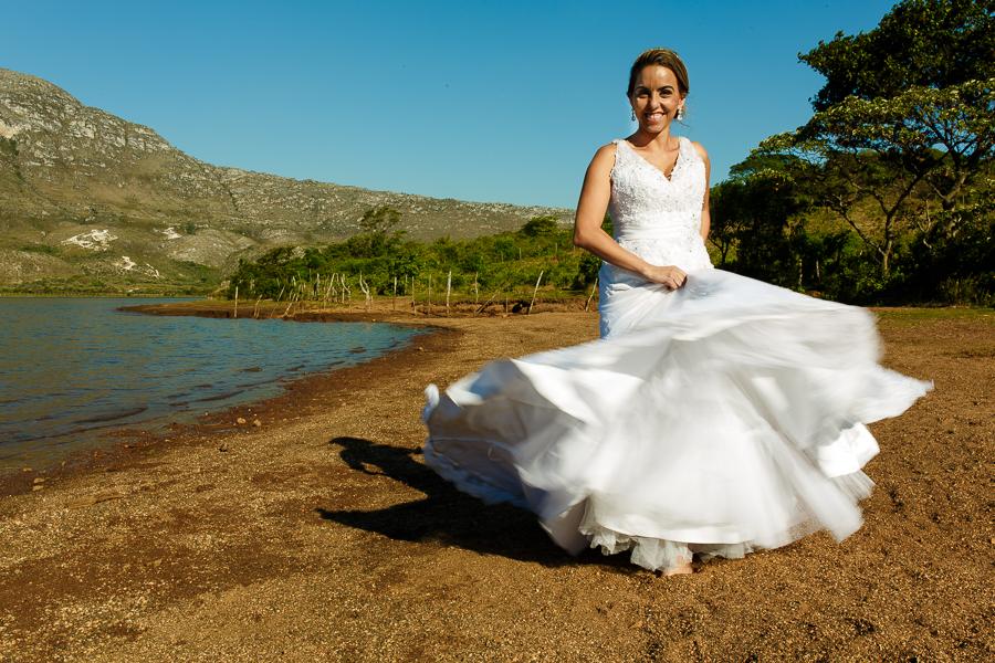 noiva josiane balancando o vestido ao lado do lago em lapinha da serra, mg