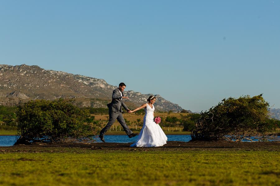 casal josiane e warley noivo pulando e segurando a mao da noiva em lapinha da serra MG