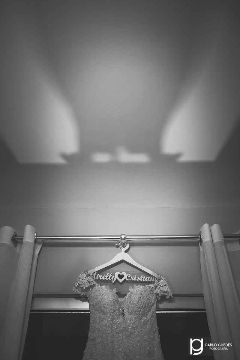 foto do vestido da noiva pendurado com sombras no teto.