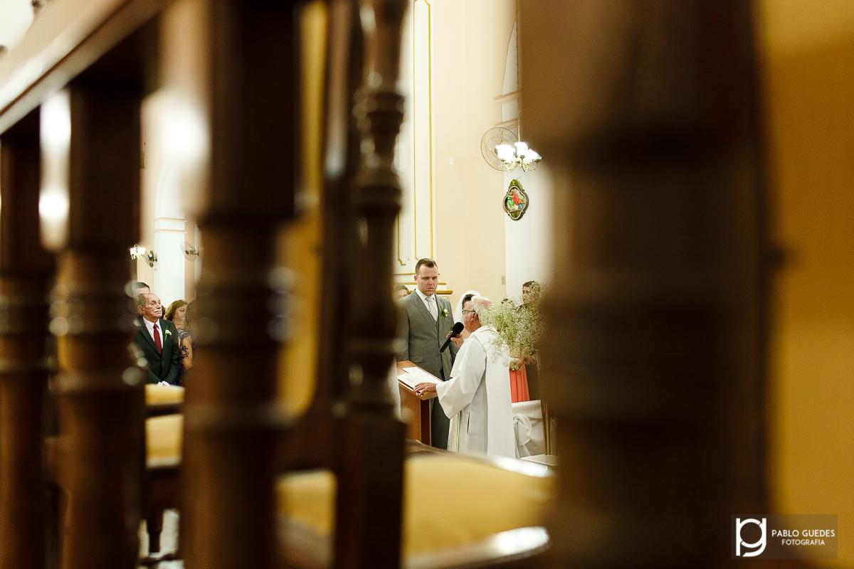 noivos e pai do noivo emoldurados por uma cadeira na cerimonia de casamento