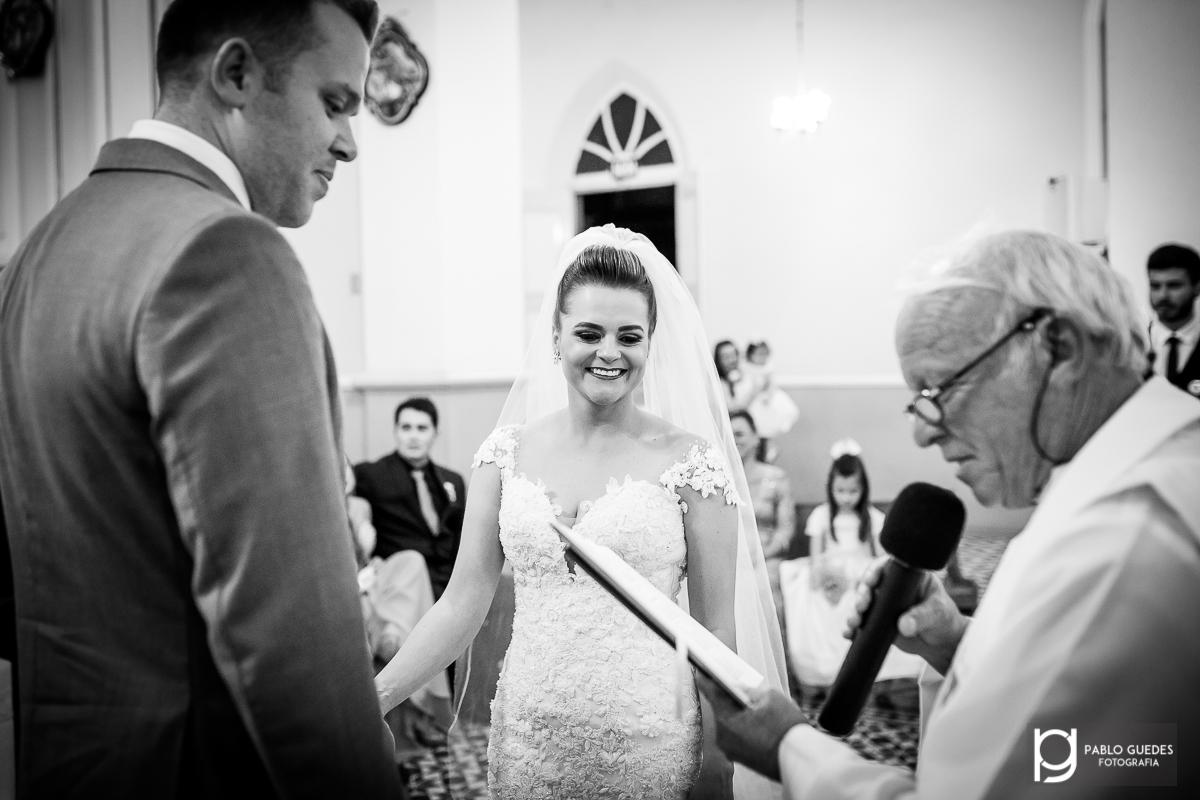 noiva mirelly segurando mao do noivo cristiano e sorrindo com leitura do padre