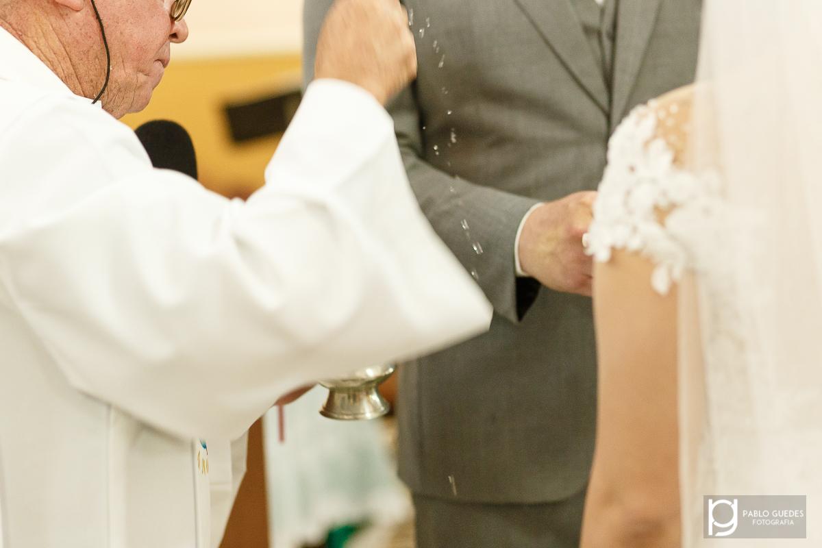 padre benzendo as alianças com agua benta da pra ver os pingos de agua no ar