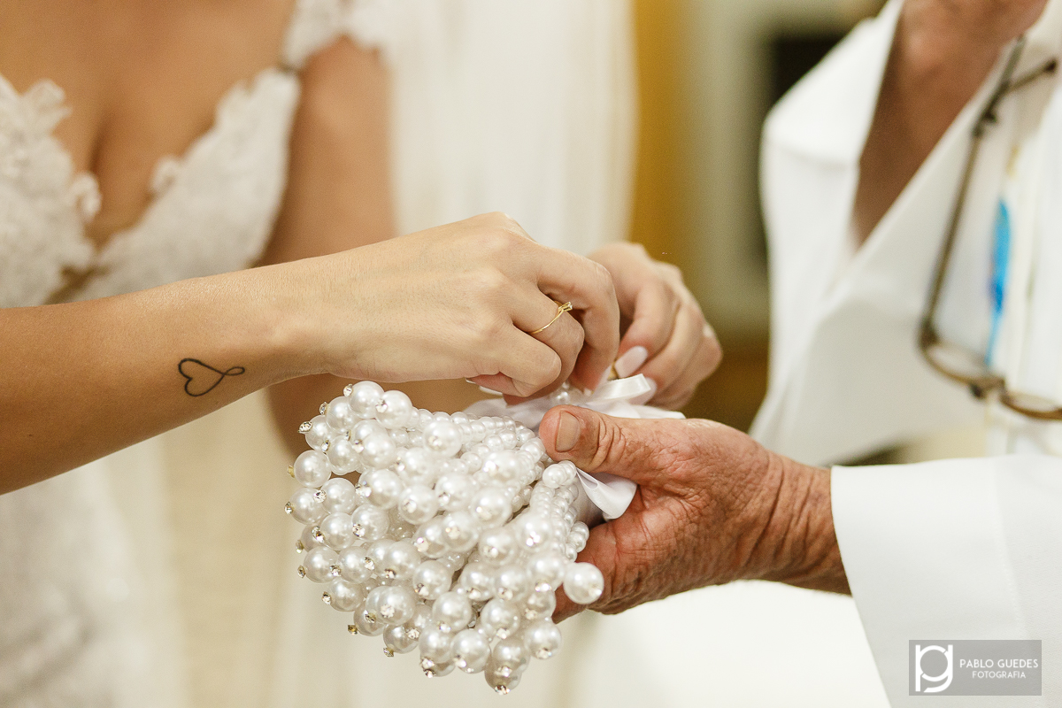 detalhe da noiva pegando as alinças no porta aliança de perola