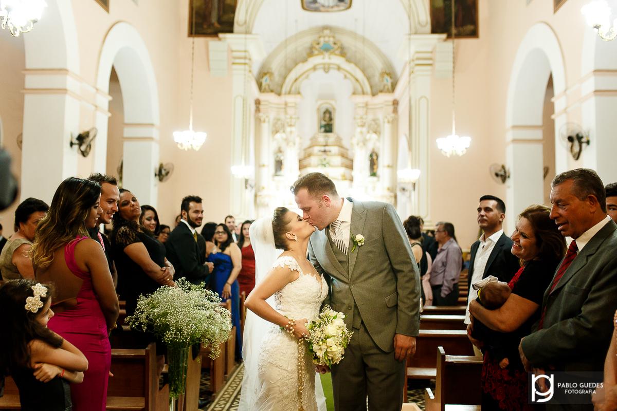 na saida da igreja noivos se beijam apos casamento