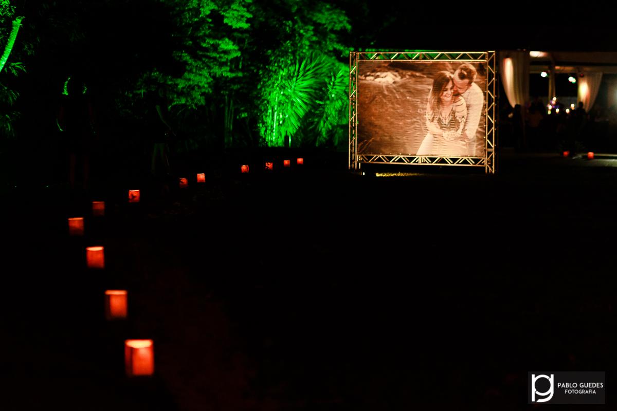 caminho de velas com foto do prewedding do casal iluminando a entrada da festa