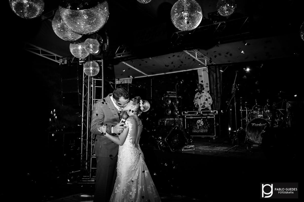 noivos se beijando no palco da festa