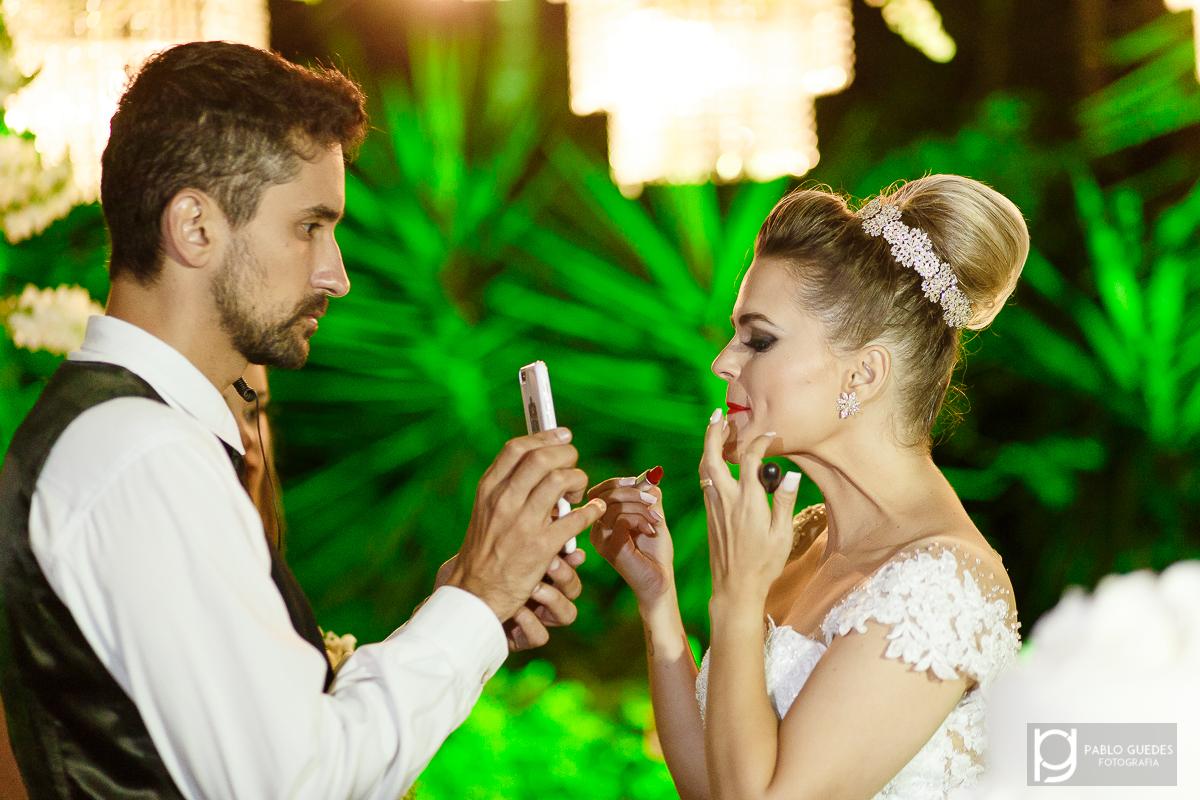 cerimonialista segurando espelho para a noiva passar baton