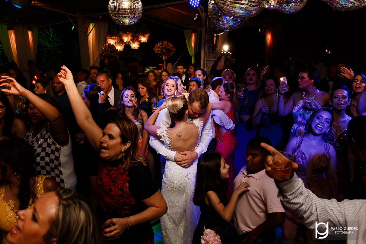noivos se beijando e convidados dançando ao redor