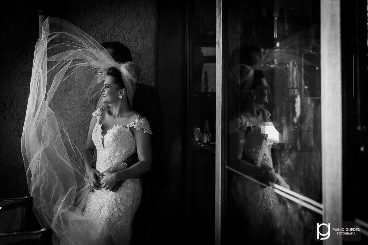 fotos externas ou trash the dress veu da noiva voando com reflexo dos noivos na janela
