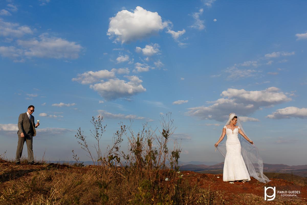 noiva fazendo pose segurando o veu e o noivo chegando a direita