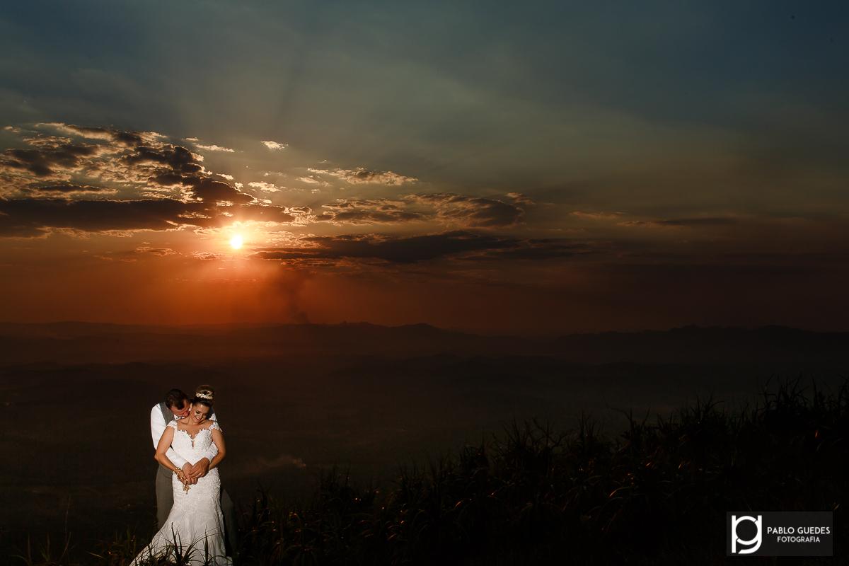 noivos se abraçando com um lindo por do sol
