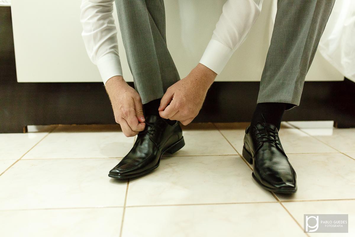 noivo cristiano calçando e amarrando os sapatos antes do casamento