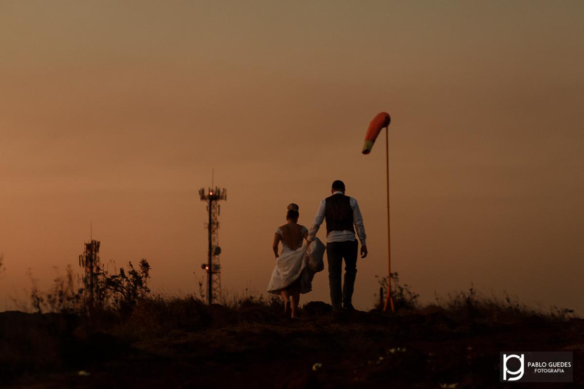 final do ensaio noivo segurando vestido da noiva nos ultimos raios de sol