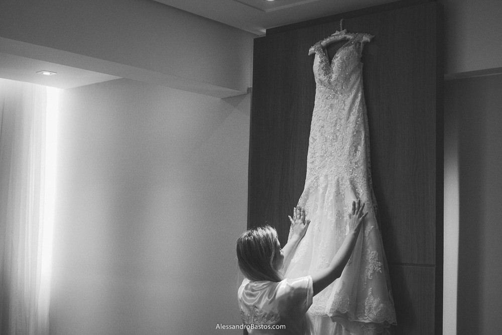 as mãos da noiva do casamento em belo horizonte bh foto acariciam o vestido pendurado no quarto onde ela fez a maquiagem