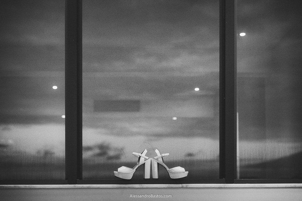 sapato da noiva do casamento em belo horizonte bh foto pendurado na janela do hotel com o sol se pondo