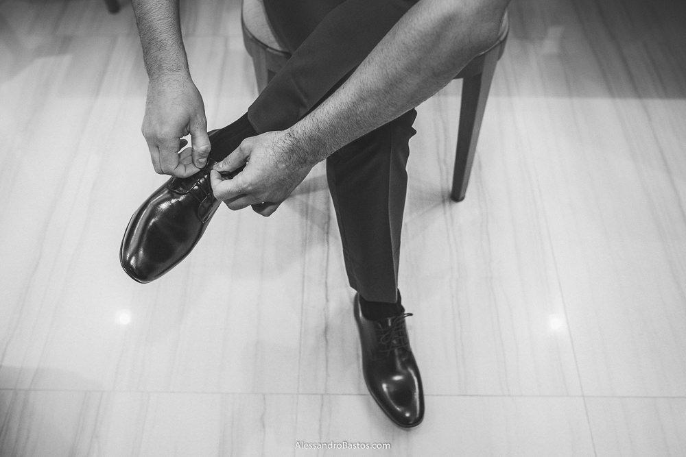 amarrando o sapato está o noivo do casamento em belo horizonte bh foto sentando em uma cadeira em sua casa