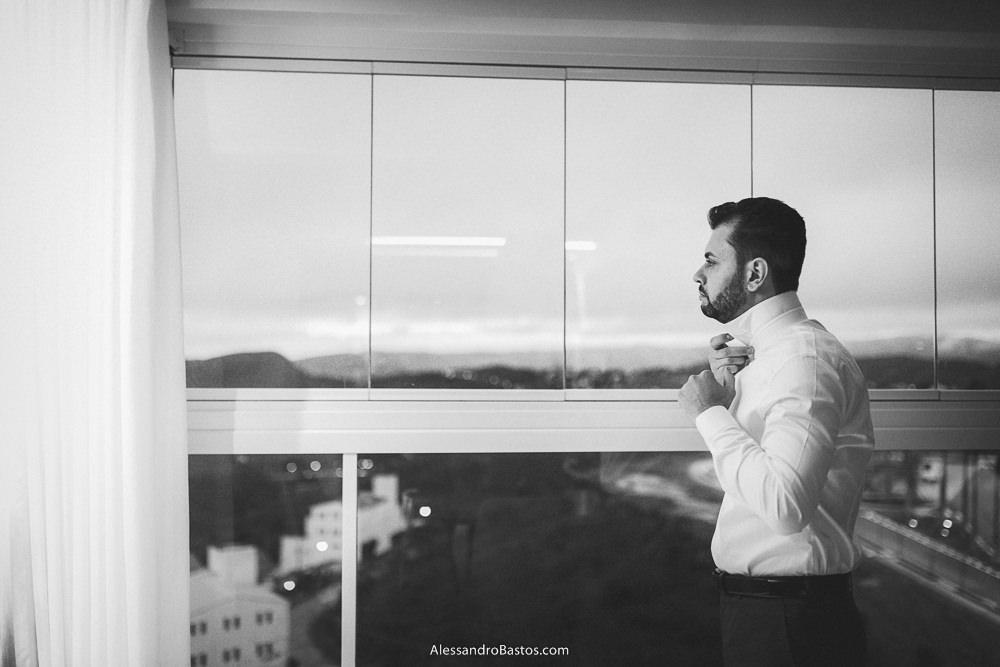 mostrando a janela ao fundo o noivo do casamento em belo horizonte bh foto arruma colarinho da camisa que escolheu