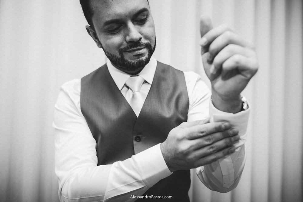abotoando as mangas da camisa está o noivo do casamento em belo horizonte bh foto e sorrindo com uma cortina no ambiente