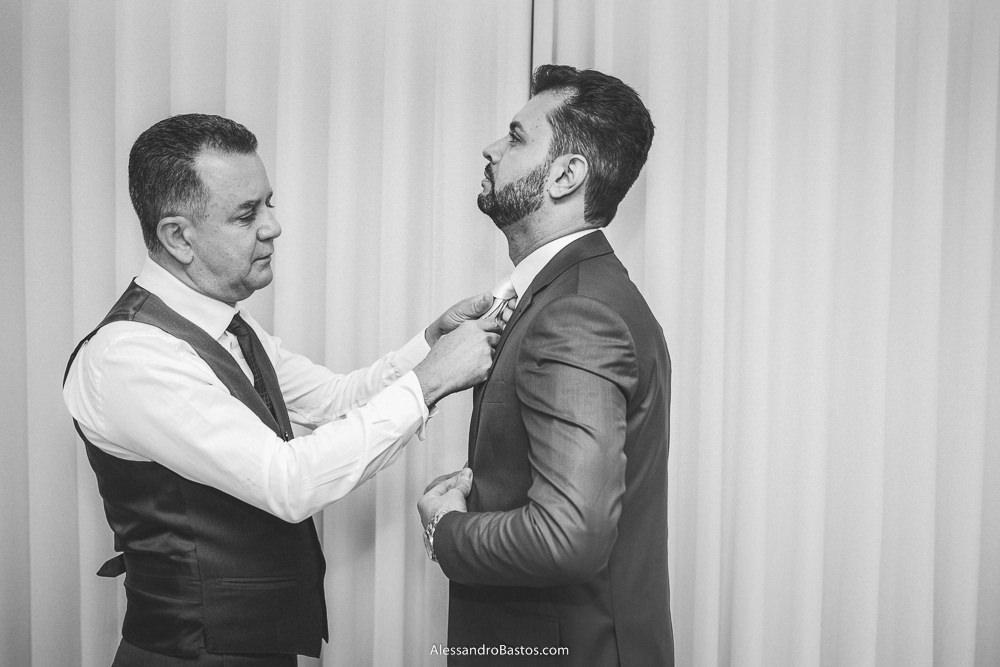 passando a mão pela gravata do noivo do casamento em belo horizonte bh foto está o pai dele para ajustar melhor no pescoço