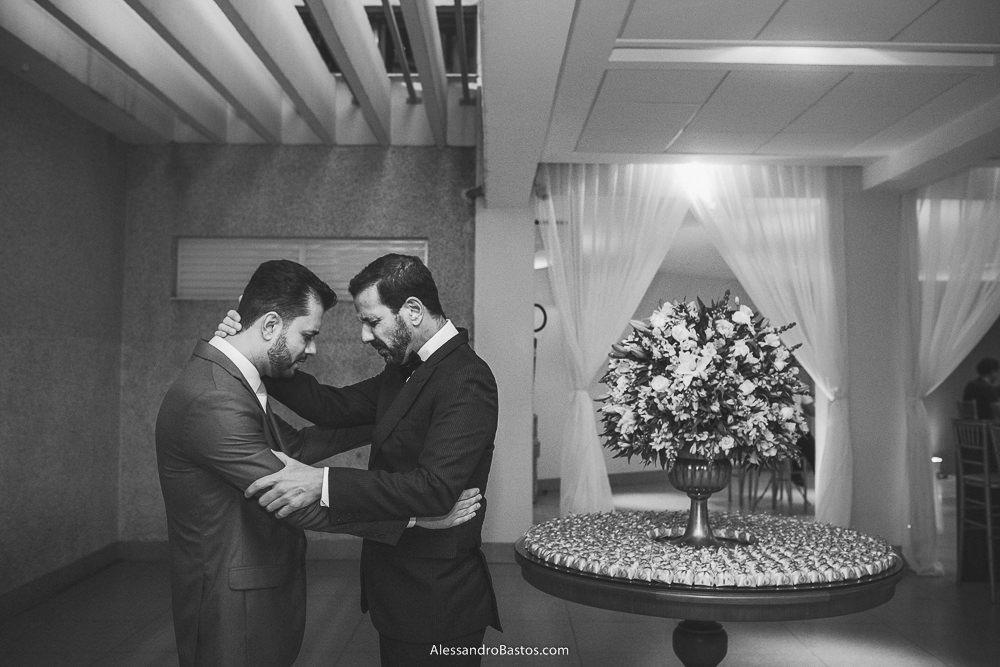padrinho do noivo do casamento em belo horizonte bh foto o abraça antes de entrar na cerimônia e com ele faz uma oração
