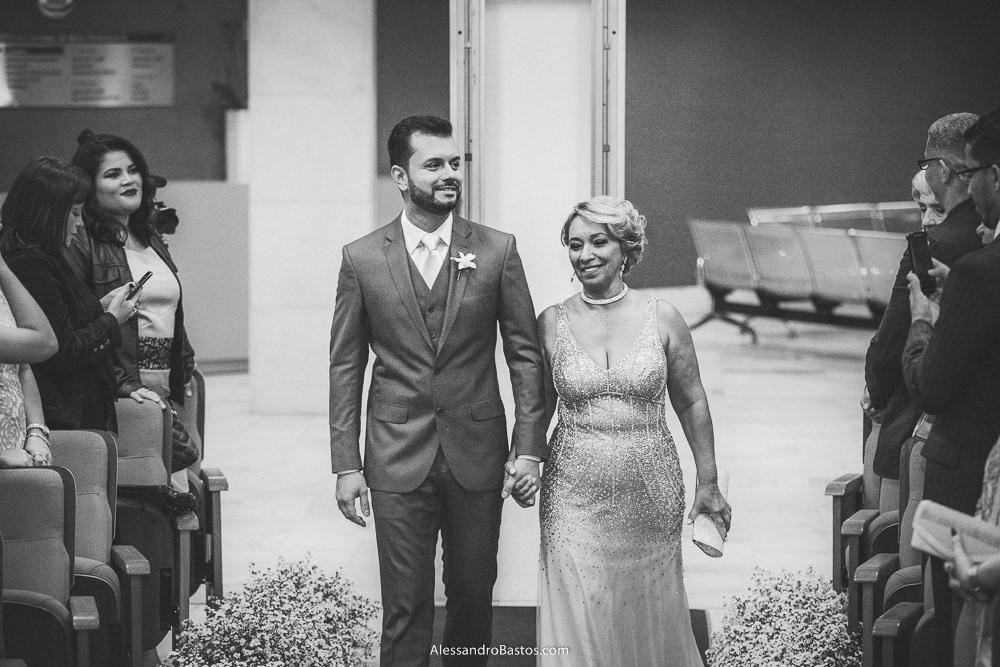 mãe do noivo do casamento em belo horizonte bh foto entra com o seu filho na cerimônia segurando uma bolsa branca