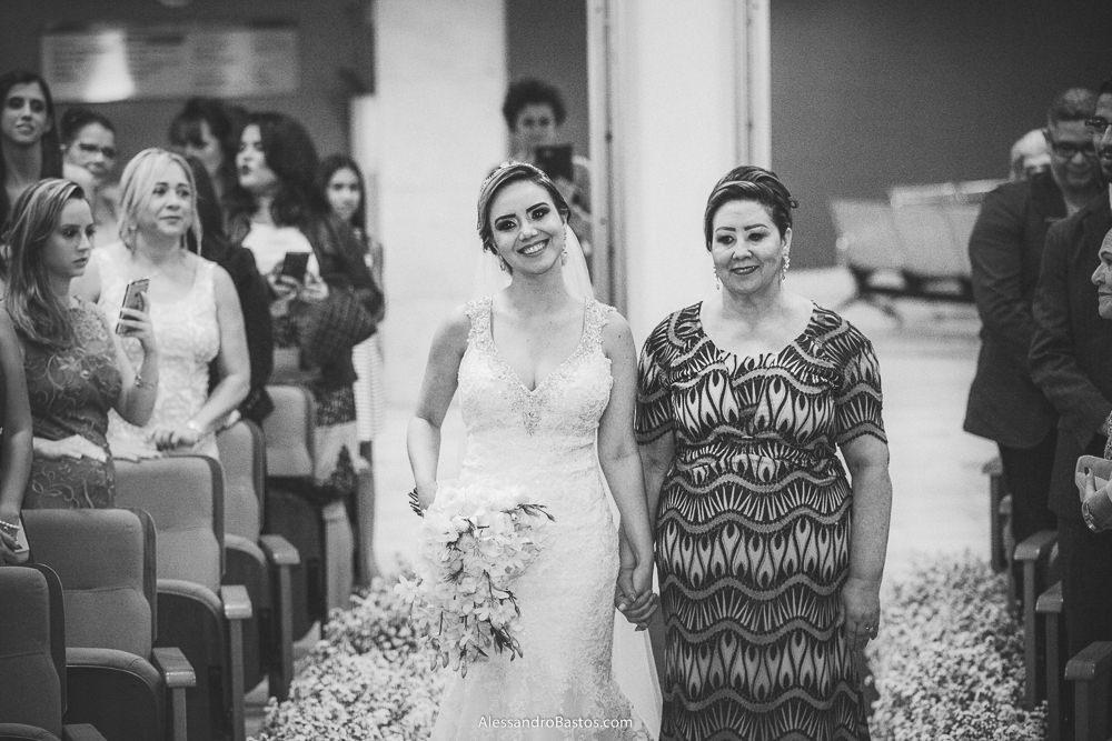 dadas as mãos estão a noiva do casamento em belo horizonte bh foto e sua mãe no corredor sorrindo muito