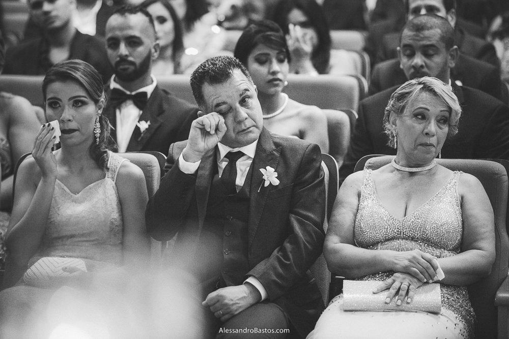 passando a mão pelos olhos mareados está o pai do noivo do casamento em belo horizonte bh foto ao lado da esposa